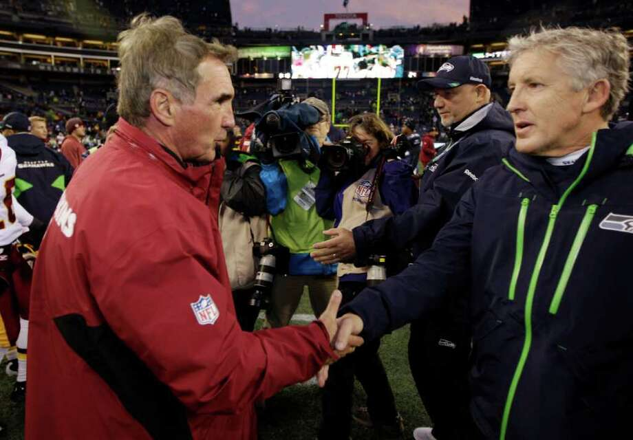 Seattle Seahawks head coach Pete Carroll, right, greets Washington Redskins head coach Mike Shanahan, left, after the Redskins won 23-17 in an NFL football game, Sunday, Nov. 27, 2011, in Seattle. Photo: AP