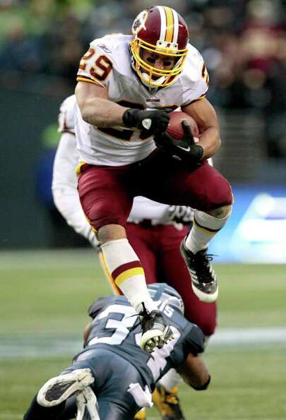 Washington Redskins' Roy Helu leaps over Seattle Seahawks' Roy Lewis on his way to a touchdown in th