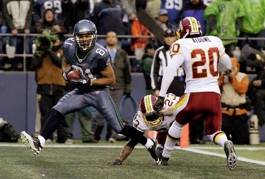 Seattle Seahawks wide receiver Golden Tate makes a touchdown reception under pressure from Washington Redskins' DeAngelo Hall (23) and Oshiomogho Atogwe (20) in the second half of an NFL football game, Sunday, Nov. 27, 2011, in Seattle. Photo: AP