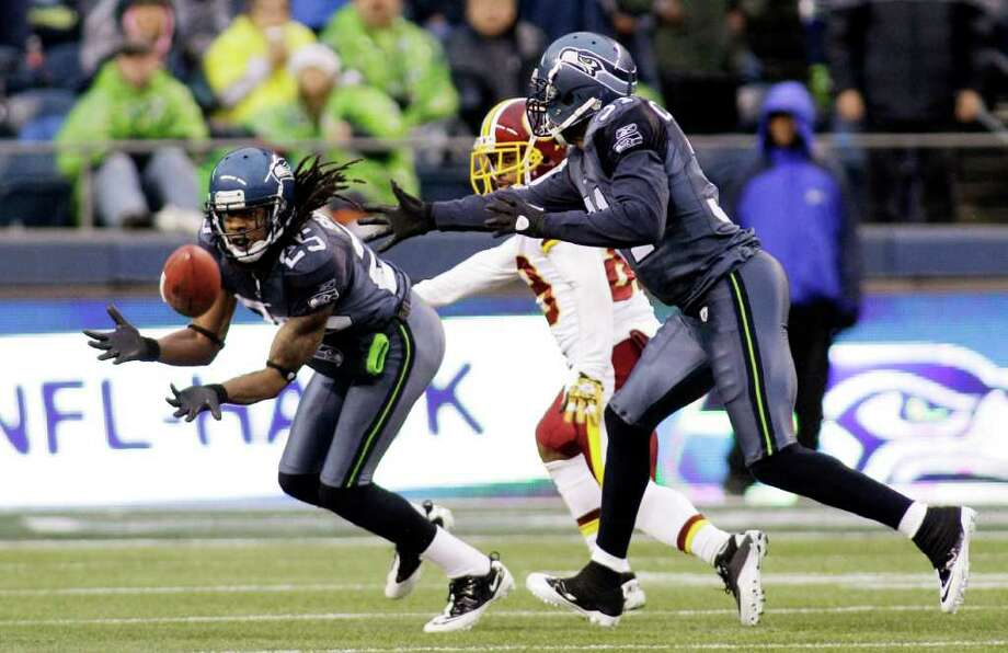 Seattle Seahawks' Richard Sherman, left, intercepts a pass meant for Washington Redskins' Santana Moss as Seahawks' Kam Chancellor follows in the second half of an NFL football game, Sunday, Nov. 27, 2011, in Seattle. Photo: AP