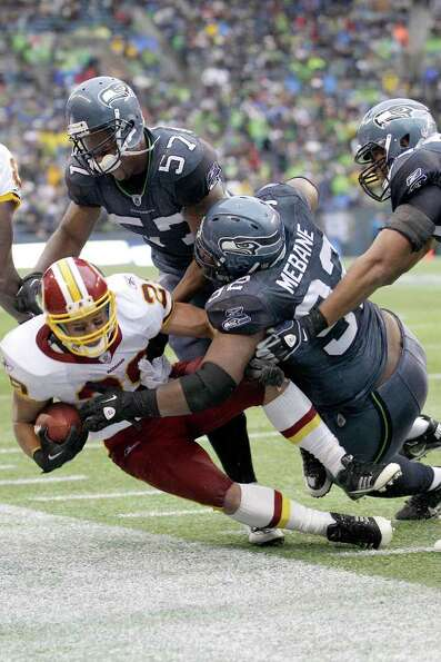 Washington Redskins Roy Helu is tackled by David Hawthorne (57) and Brandon Mebane (92) in the first