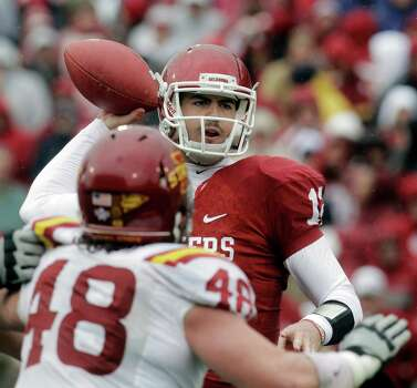 Oklahoma quarterback Landry Jones (12) passes under pressure from Iowa State's Jake Lattimer (48) in the second quarter of an NCAA college football game in Norman, Okla., Saturday, Nov. 26, 2011. Photo: Sue Ogrocki, Associated Press / AP