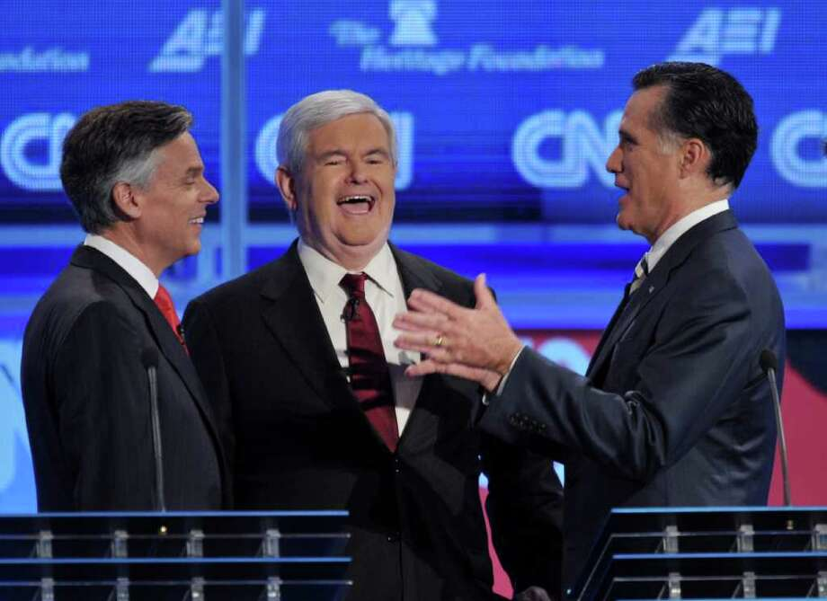 ASSOCIATED PRESS FILE WORTH A SMILE: Newt Gingrich, center, and Mitt Romney, right, confer with Jon Huntsman prior to the start of the Republican presidential debate last week.  On Sunday, Gingrich bested Romney when he won the endorsement of the largest newspaper in New Hampshire. Photo: MANDEL NGAN / AFP