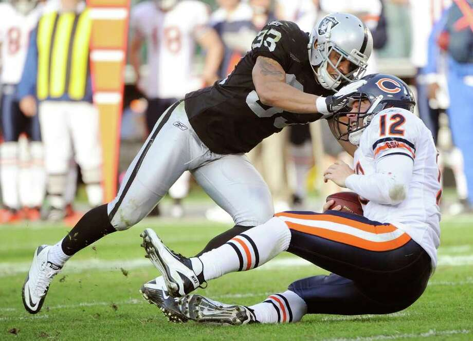 THEARON W. HENDERSON: GETTY IMAGES RUDE WELCOME: Oakland's Tyvon Branch shoves new Bears starting quarterback Caleb Hanie to the turf in the first half of the Raiders' win Sunday. Photo: Thearon W. Henderson / 2011 Getty Images