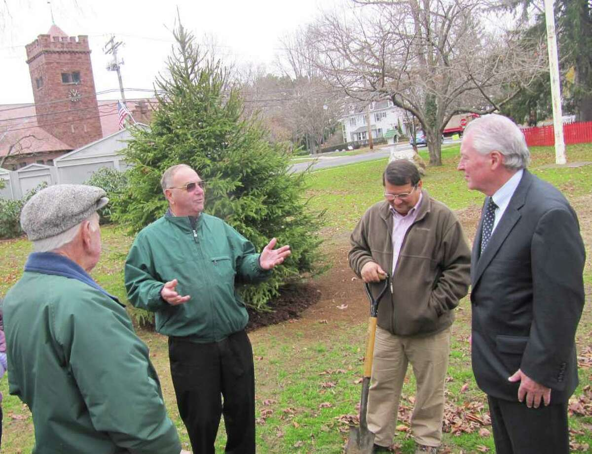 First Selectman Michael Tetreau, at right, listens to Warren Jacques, a member of the Board of Directors of the Tree Wardens' Association of Connecticut, during a ceremony in which a