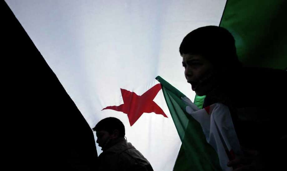 Children of Syrian ascent  shout slogans as they walk under giant revolutionary Syrian flag during a rally against the regime of Syrian President Bashar al-Assad in front of the Syrian embassy in Sofia, on Sunday, Nov. 27, 2011. More than 3,500 people have died in months of anti-government protests in Syria, according to the UN. (AP Photo/Valentina Petrova) Photo: Valentina Petrova / AP