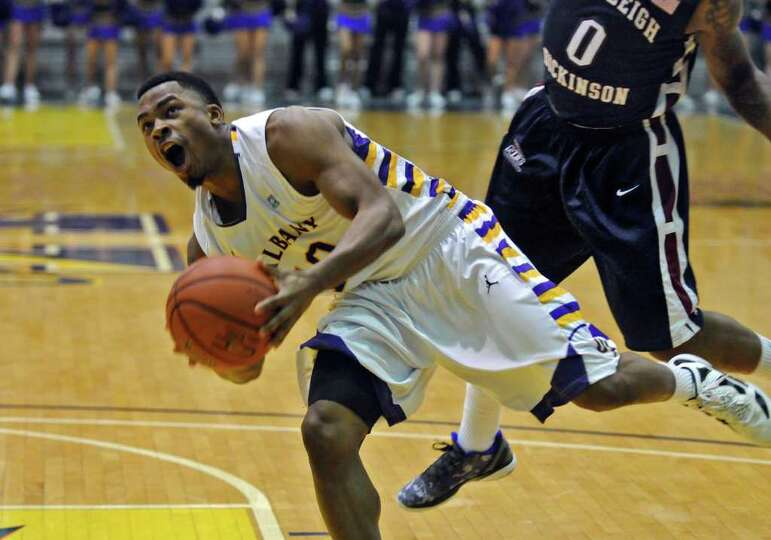 UAlbany's Mike Black collides with Fairleigh Dickinson's Lonnie Hayes while driving to the basket du