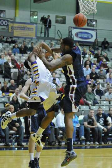 UAlbany's Mike Black is fouled by Fairleigh Dickinson's George Goode, right, during the second half