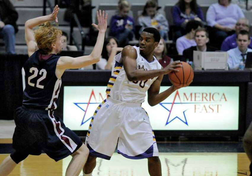 UAlbany's Jayson Guerrier, right, is defended by Fairleigh Dickinson's Mathias Seilund, left, during