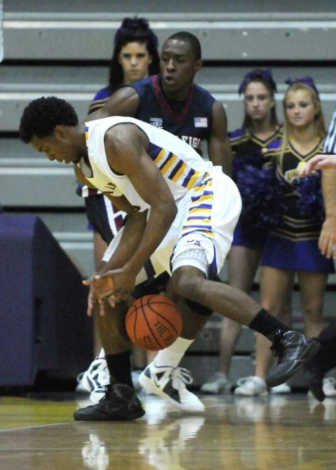 UAlbany's Gerardo Suero is defended by Fairleigh Dickinson's Lonnie Robinson, right, during the second half of UAlbany's 81-62 victory at the SEFCU Arena on Sunday Nov. 27, 2011 in Albany, NY. (Philip Kamrass / Times Union ) Photo: Philip Kamrass / 00015354A