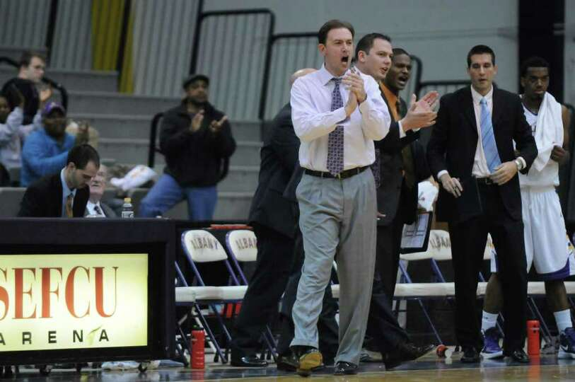 UAlbany head coach Will Brown cheers on his team at the end of the first half of their 81-62 victory