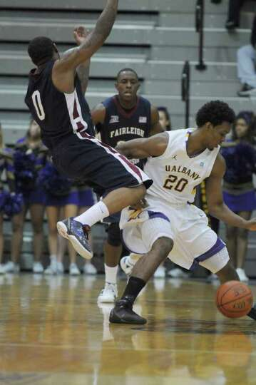 UAlbany's Gerardo Suero, right,  is fouled by Fairleigh Dickinson's Lonnie Hayes, left, during the s