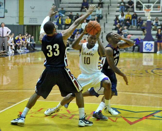UAlbany's Mike Black drives to the basket past Fairleigh Dickinson's Briahn Smith, left, and Lonnie