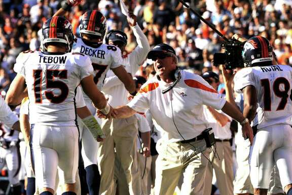 Denver Broncos coach John Fox celebrates quarterback Tim Tebow on a touchdown pass to wide receiver Eric Decker (87) in the first half of an NFL football game against San Diego Chargers on Sunday, Nov. 27, 2011, in San Diego. (AP Photo/The Denver Post, Joe Amon) MAGS OUT  TV OUT