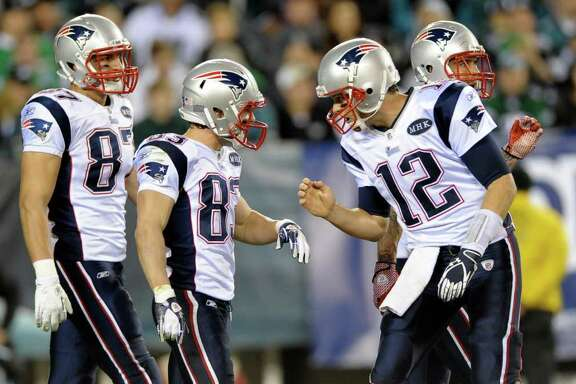New England Patriots quarterback Tom Brady, right, reacts with wide receiver Wes Welker, second from left, and tight end Rob Gronkowski (87), left, after Welker's touchdown during the first half of an NFL football game against the Philadelphia Eagles, Sunday, Nov. 27, 2011, in Philadelphia. (AP Photo/Michael Perez)