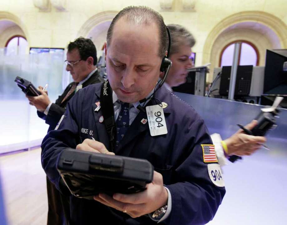 FILE - In the file photograph taken Nov. 9, 2011, trader Michael Urkonis, center, works on the floor of the New York Stock Exchange. Global stocks advanced Monday, Nov. 28, 2011, as further proposals to get a grip on Europe's debt crisis were touted amid signs that the U.S. Christmas shopping season has started off strongly. (AP Photo/Richard Drew, File) Photo: Richard Drew / AP2011
