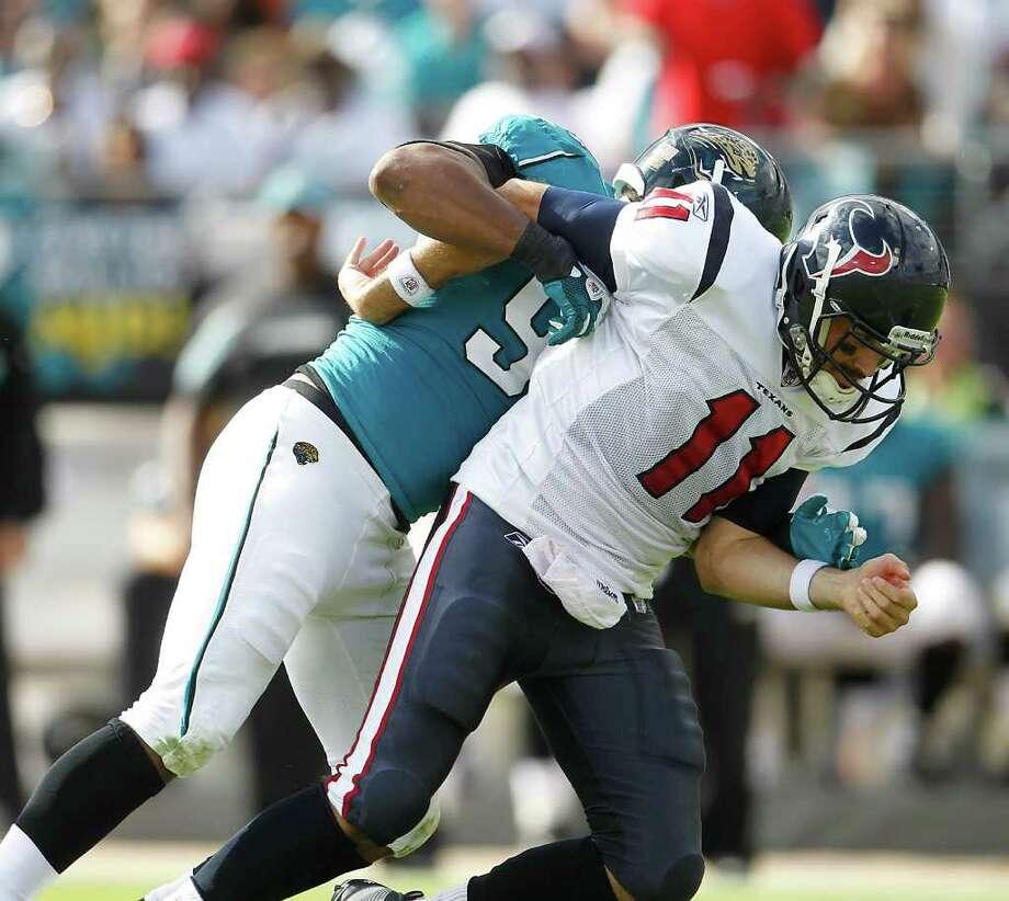 El quarterback de los Texans Matt Leinart (11) es tomado del brazo por el jugador de Jacksonville Jaguars Jeremy Mincey (94) y se lesiona durante la victoria del domingo de Houston en el EverBank Field de Jacksonville, Florida. Photo: Karen Warren / © 2011 Houston Chronicle