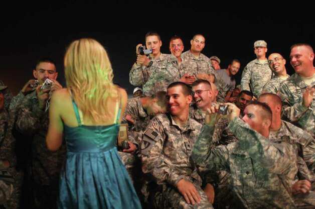 BAGHDAD - SEPTEMBER 15:  U.S. troops watch as a Dallas Cowboys Cheerleader sings during a show as part of a military USO tour of Iraq September 15, 2007 in Baghdad, Iraq. The cheerleaders are on their first trip to Iraq and are doing five shows throughout the country for the soldiers, many of whom are on 15 month deployments. Photo: John Moore, Getty Images / 2007 Getty Images