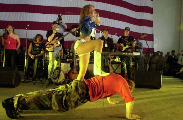 ABOARD USS NIMITZ - JUNE 19:   A Dallas Cowboys Cheerleader performs during a United Services Organization (USO) show  while a crewmember does push-ups  aboard the USS Nimitz  June 19, 2002 in the Arabian Gulf. Photo: U.S. Navy, Getty Images / 2003 U.S. Navy