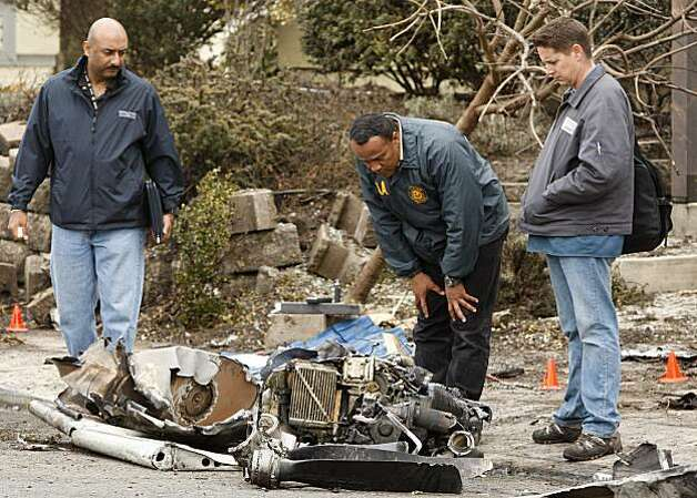 National Transportation Safety Board investigators look over engine, propeller, and wing wreckage Thursday, Feb. 18, 2010, in East Palo Alto, Calif. Federal investigators are examining the site of a twin-engine Cessna 310 that crashed after taking off from a nearby airport shrouded in fog into a Silicon Valley neighborhood yesterday, killing three employees of electric car maker Tesla Motors. (AP Photo/Ben Margot) Photo: Ben Margot, AP