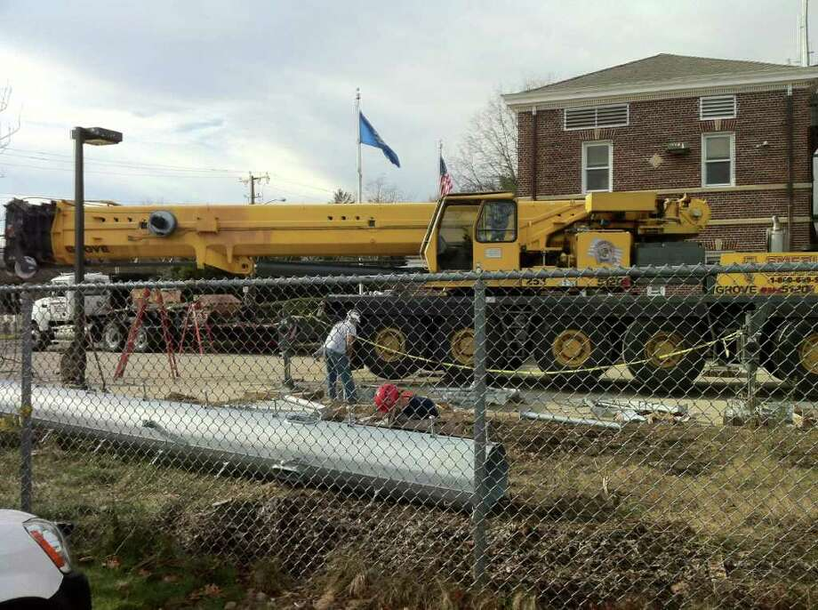 Workers prepare to install the new communications tower at the Darien Police Department Nov. 28. Photo: Ben Holbrook