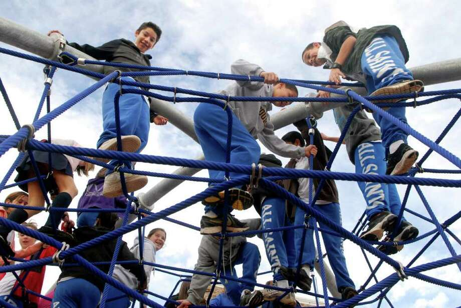Students climb on the jungle gym in the new playground at All Saints Catholic School in Norwalk, Conn. on Monday November 28, 2011 before the arrival of Bishop Lori of the Diocese of Bridgeport who came to bless the playground. Photo: Dru Nadler / Stamford Advocate Freelance