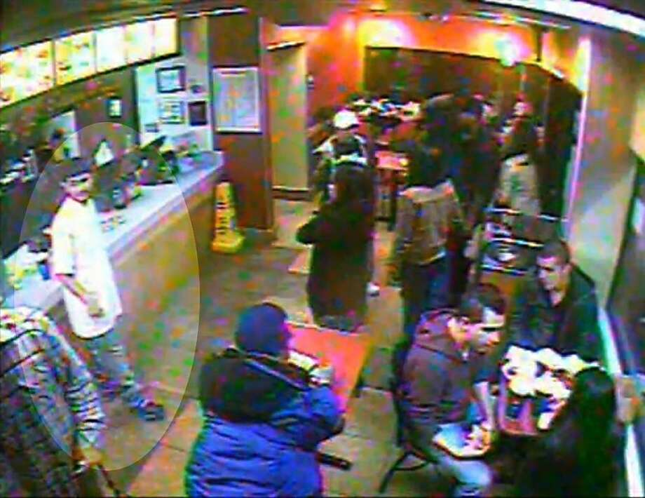 The suspect, wearing a white t-shirt, a mixed race or Latino male, 18 to 24 years old, with short black hair and a manicured beard at the counter of the Jack in the Box at 11th and Geary on Thanksgiving Day. San Francisco police released a videotape Sunday of the man who deliberately ran over a state firefighter at a Geary Boulevard gas station on Thanksgiving Day after a fight at the Jack in the Box. Photo: San Francisco Police Dept.