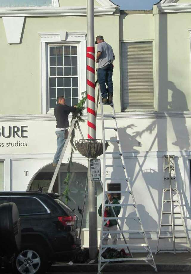 Downtown Westport looked a little more colorful Monday as workers hired by the Dwontown Merchants Association added holiday colors to light poles. The work is expected to be completed sometime Wednesday. Photo: Kirk Lang
