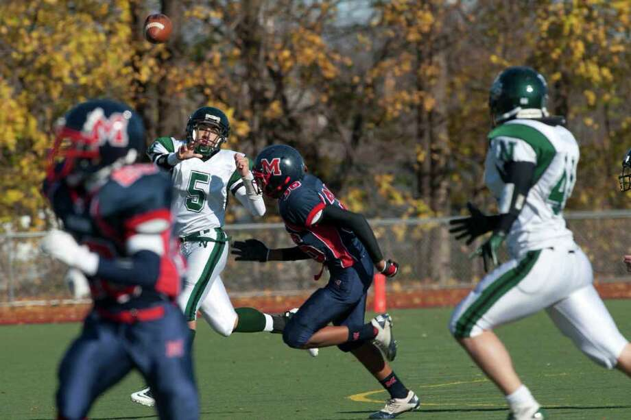 Norwalk's QB Deishawn Wilson throws a compleated pass to Gil Araujo against McMahon during high school football action, at Brien McMahon,Thursday Nov. 24, 2011. Photo: Douglas Healey / Stamford Advocate