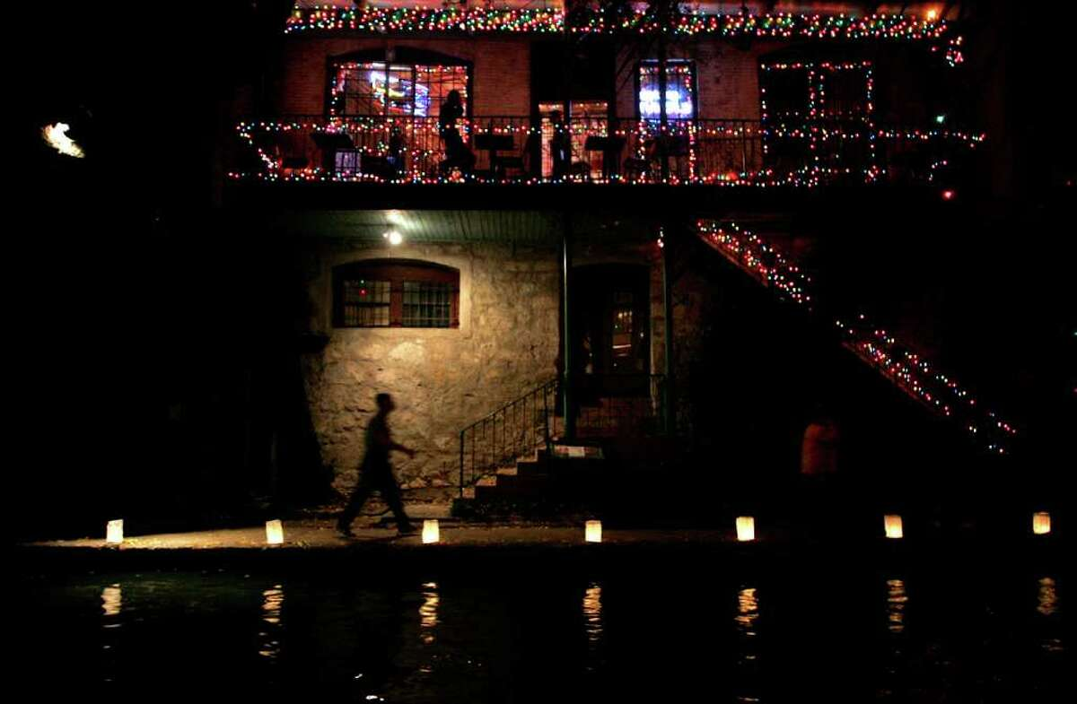 A man walks past the Esquire Tavern on the River Walk Friday Dec. 2, 2005. Luminarias were placed along the river in preparation for the Fiesta de Las Luminarias. (MIKE KANE/ STAFF)