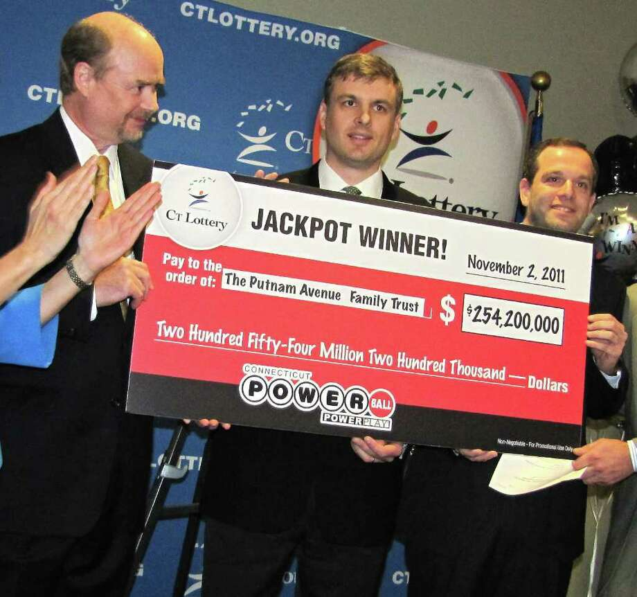 Greenwich asset managers, from left, Tim Davidson, Greg Skidmore and Brandon Lacoff pose in Rocky Hill Monday with a symbolic check from CT Lottery representing the $254 million they won in the Powerball lottery. Photo: Contributed Photo / Stamford Advocate Contributed