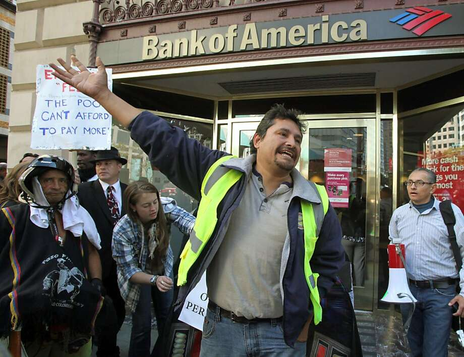 "Mario Brito joins other Occupy Los Angeles demonstrators as they march to a Bank Of America branch, Tuesday, Nov. 8, 2011, in downtown Los Angeles. The protests continue to draw large crowds and fresh participants as similar ""Occupy Wall Street"" protests are spreading around the world. (AP Photo/Reed Saxon)  Ran on: 11-13-2011 Occupy protesters in Los Angeles and around the country helped persuade Bank of America to drop a debit-card fee. Ran on: 11-13-2011 Occupy protesters in Los Angeles and around the country helped persuade Bank of America to drop a debit-card fee. Ran on: 11-13-2011 Occupy protesters in Los Angeles and around the country helped persuade Bank of America to drop a debit-card fee. Photo: Reed Saxon, AP"