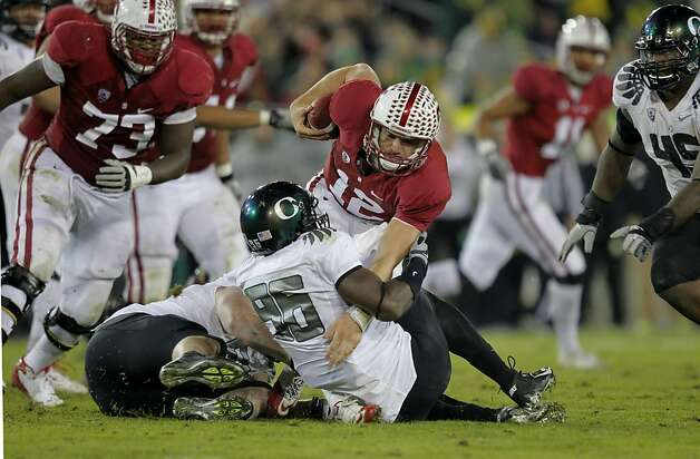 Stanford's Andrew Luck (12) is sacked by Oregon's Taylor Hart(66) and Dion Jordan(96) in the third quarter, as the Stanford Cardinal go on to lose to the  Oregon Ducks 53-30 at Stanford Stadium, on Saturday November 12, 2011 in Palo Alto, Ca. Photo: Michael Macor, The Chronicle