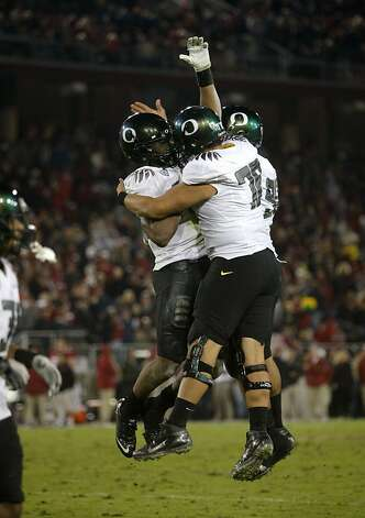 Oregon's Boseko Lokombo(25), (left)  celebrates his interception touchdown in the fourth quarter, as the Stanford Cardinal go on to lose to the  Oregon Ducks 53-30 at Stanford Stadium, on Saturday November 12, 2011 in Palo Alto, Ca. Photo: Michael Macor, The Chronicle