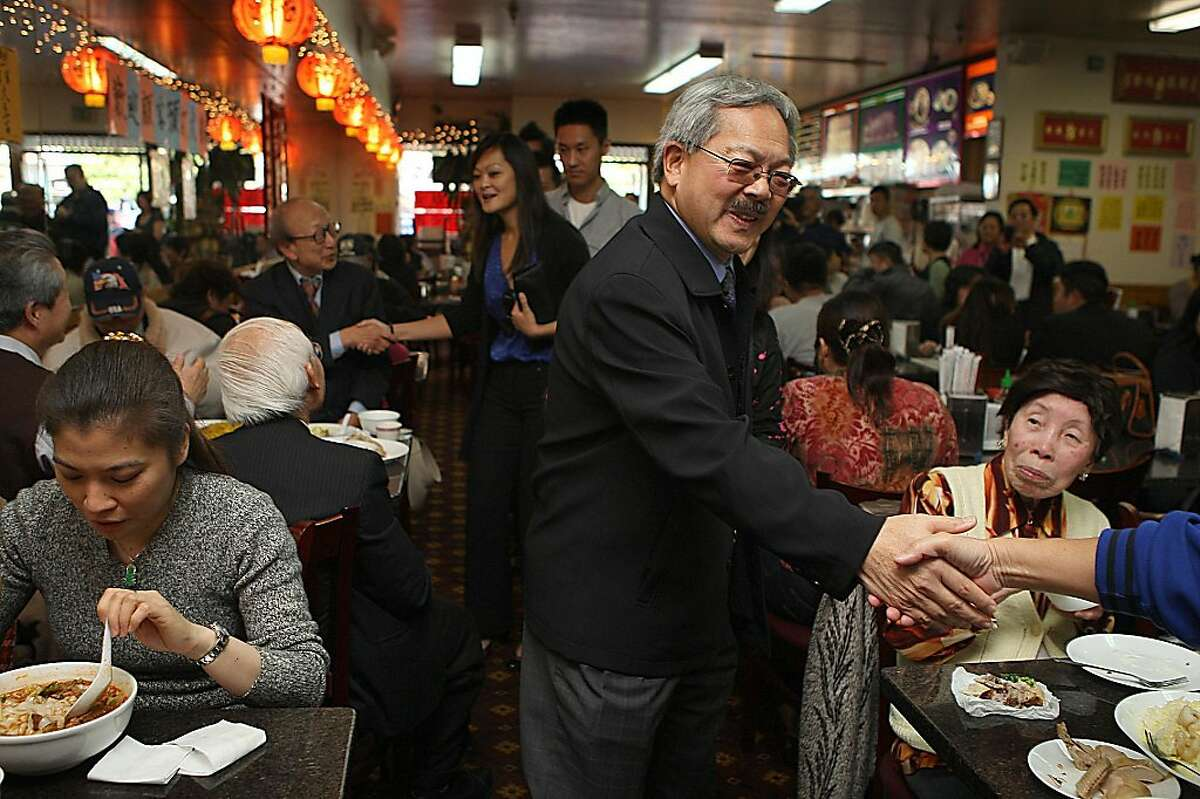 Mayor Ed Lee (middle) and supervisor Carmen Chu (back, middle) greeting the lunch crowd at Lam Hoa Thuan during a merchant walk on Irving St. in San Francisco, Calif., on Thursday, November 10, 2011.