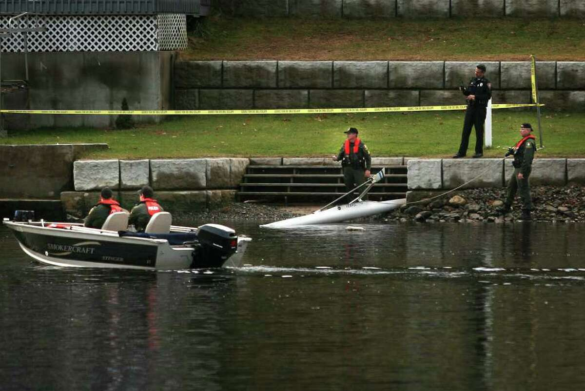 State DEEP and local police officers stand by a single rowing scull that was found capsized in the Housatonic River in the vicinity of 64 Birchbank Road in Shelton on Monday, November 28, 2011.