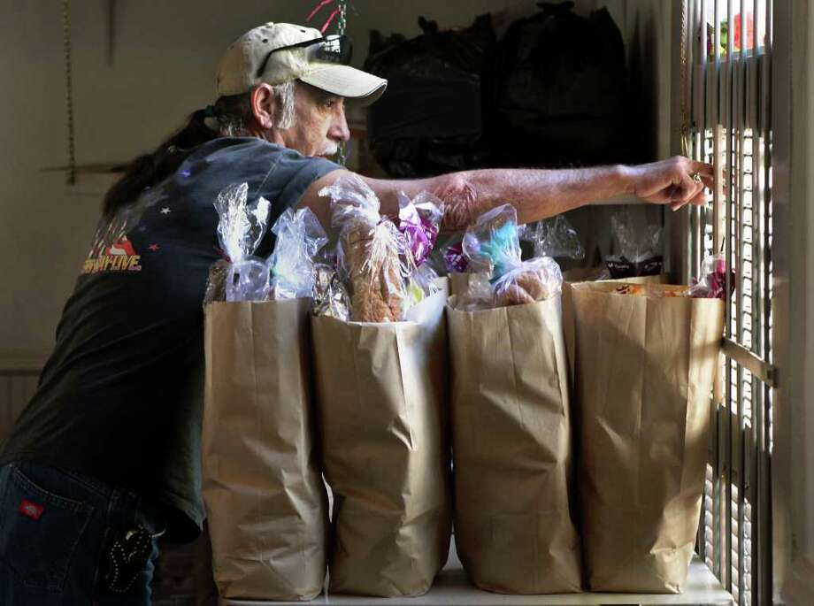 John Gray, a volunteer at the Little Church of La Villita, looks outside to see how many are waiting for food, after he and his wife Mary Gray filled bags with food to be handed out at the church.  Monday, Nov. 28, 2011. Photo Bob Owen/rowen@express-news.net Photo: BOB OWEN, SAN ANTONIO EXPRESS-NEWS / rowen@express-news.net