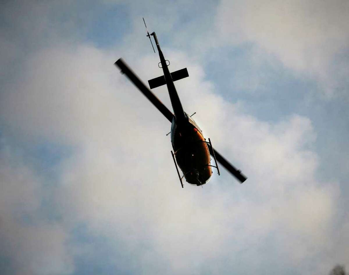 A helicopter searches above the Housatonic River between Oxford and Shelton for a missing man after a capsized single rowing scull was found in the vicinity of 64 Birchbank Road in Shelton on Monday, November 28, 2011.