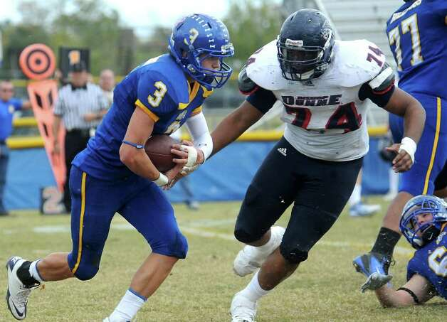 Kelly's Dillon Guidroz carries the ball as Bishop Dunne Alex Norman looks to make the stop at Kelly High School in Beaumont, Saturday, November 12, 2011. Photo: TAMMY MCKINLEY