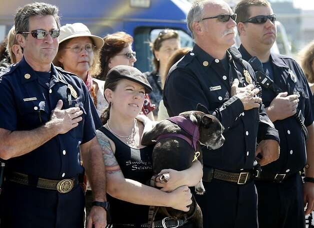 Andie Ferman and her dog Sally joined members of the Alameda fire department during the national anthem.  Ferman works at the nearby St. George Spirits tasting room. The City of Alameda and the Department of the Navy have come to an agreement for the city to take over 918 acres of the former Naval Air Station now called Alameda Point. Photo: Brant Ward, The Chronicle