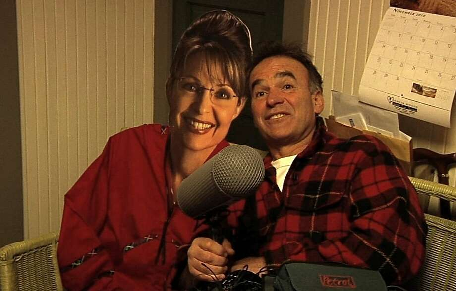 """In this film image released by the Freestyle Releasing, director Nick Broomfield poses with a cardboard cut-out of former Republican Vice Presidential candidate Sarah Palin in a scene from the documentary """"Sarah Palin: You Betcha!"""" The film is being presented at the Toronto International Film Festival. (AP Photo/ Freestyle Releasing) Photo: Freestyle Releasing, AP"""