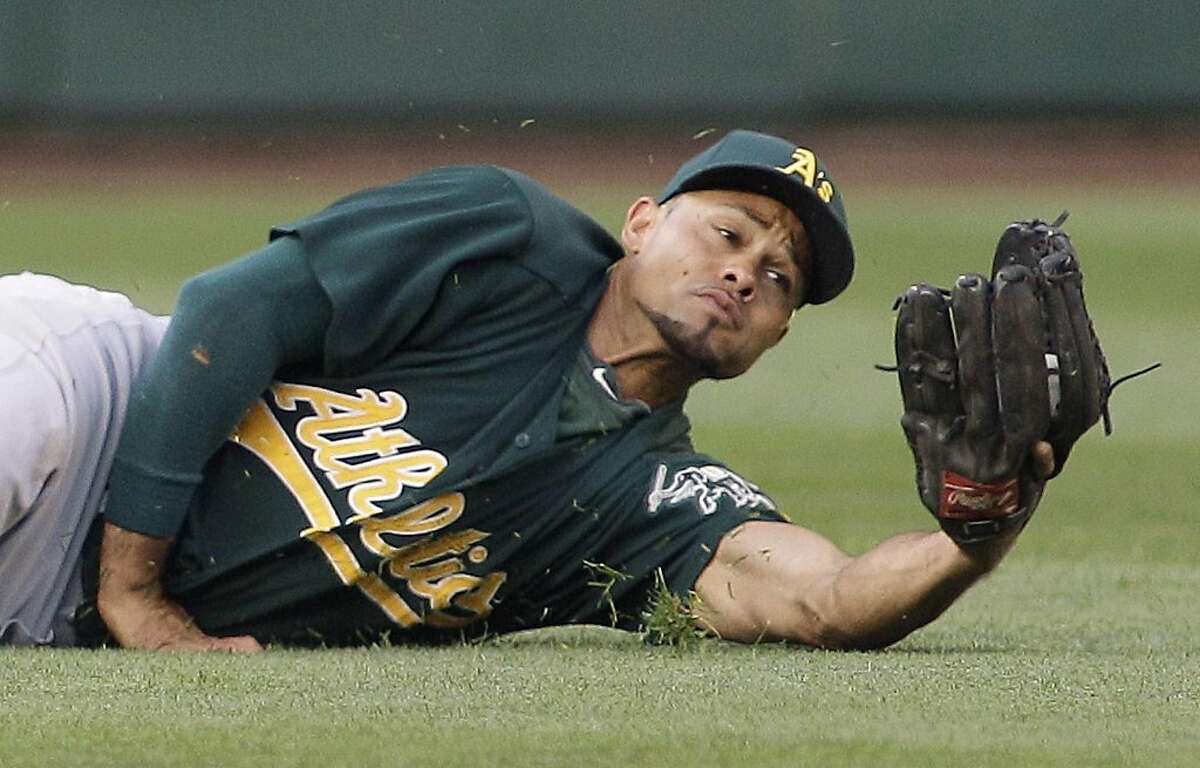 Oakland Athletics center fielder Coco Crisp makes a diving catch of a ball hit by Seattle Mariners' Ichiro Suzuki in the third inning of a baseball game Tuesday, Aug. 2, 2011, in Seattle. (AP Photo/Ted S. Warren)
