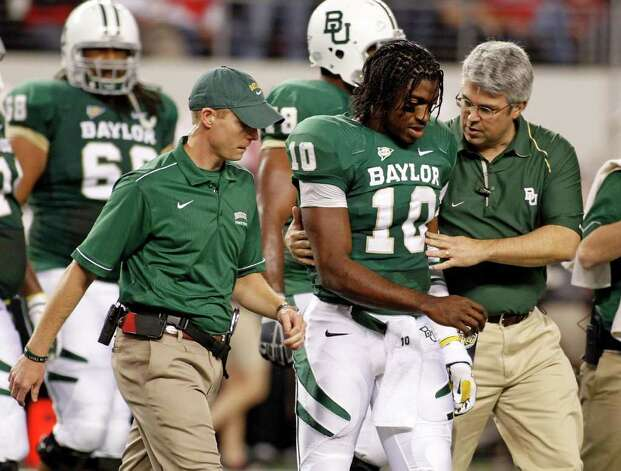 Baylor quarterback Robert Griffin III (10) is helped off the field by training staff after a hit in the second quarter of an NCAA college football game Saturday, Nov. 26, 2011, in Arlington, Texas. Baylor won 66-42. Photo: AP