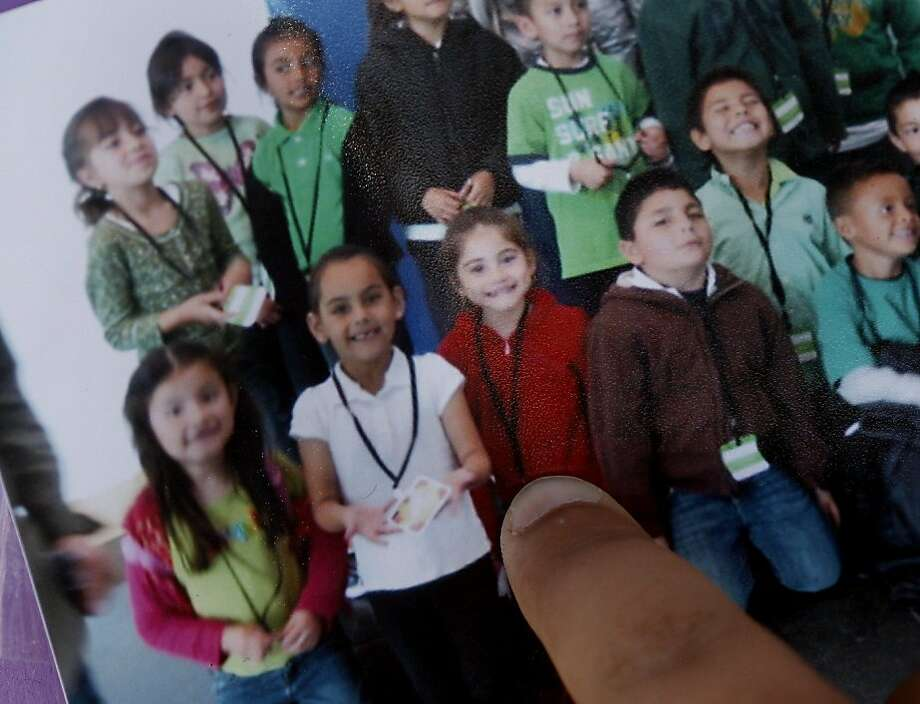 The young schoolchild victim known Sioreli is identified by a classmate in a school picture.  She is the third from left, bottom row, in red. Two fatalities were reported in East Palo Alto Wednesday September 28, 2011.  The first when an SUV being chased by police ran into a motorcyclist killing him, the second when a young schoolgirl was run over in a crosswalk only a few blocks away. Photo: Brant Ward, The Chronicle