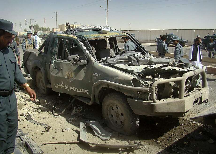 An Afghan police officer, left, looks at a police vehicle damaged in a suicide attack in Lashkar Gah, Helmand province, Afghanistan, Tuesday, Sept. 27, 2011. A suicide bomber rammed a car packed with explosives into a police truck outside a bakery in southern Afghanistan on Tuesday, killing a number of civilians, officials said. (AP Photo/Abdul Khaleq) Photo: Abdul Khaleq, AP