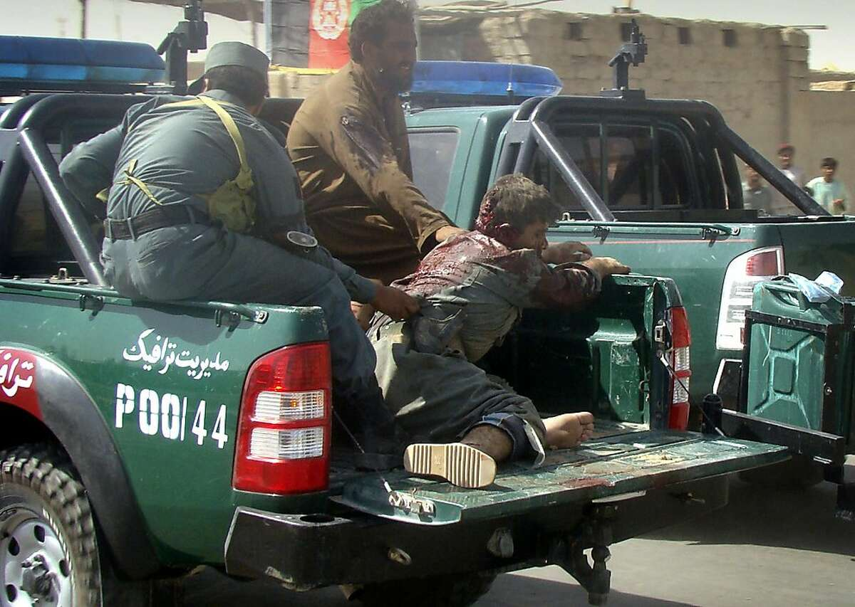An injured Afghan police officer is transported on the back of a vehicle after a suicide attack in Lashkar Gah, Helmand province, Afghanistan, Tuesday, Sept. 27, 2011. A suicide bomber rammed a car packed with explosives into a police truck outside a bakery in southern Afghanistan on Tuesday, killing a number of civilians, officials said. (AP Photo/Abdul Khaleq)