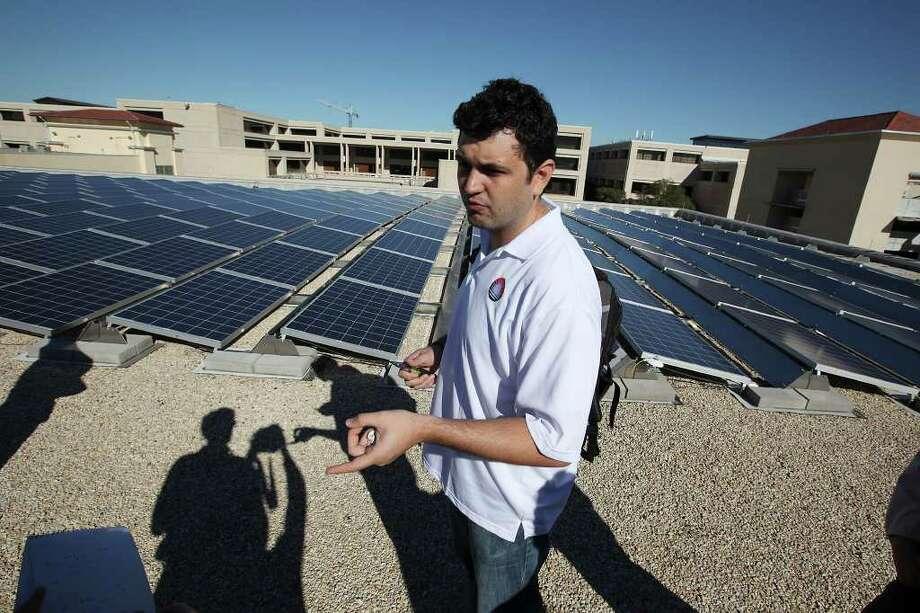 Student Gerardo Trevino shows off the University of Texas at San Antonio's new solar system. Photo: JERRY LARA, San Antonio Express-News / SAN ANTONIO EXPRESS-NEWS
