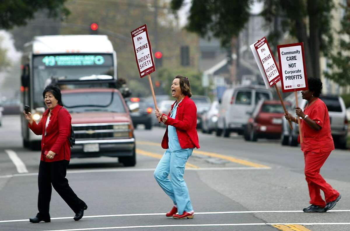 Nurses on a one-day strike at Alta Bates Summit Medical Center walk across Ashby Avenue in Berkeley, Calif. on Thursday, Sept. 22, 2011.