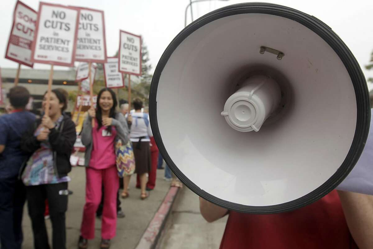 A nurse on strike uses a bullhorn to get her message across during a one-day walkout at Alta Bates Summit Medical Center in Berkeley, Calif. on Thursday, Sept. 22, 2011.