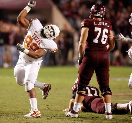 Texas Longhorns defensive lineman Desmond Jackson (99) celebrates after sacking Texas A&M Aggies quarterback Ryan Tannehill (17) during the second half of the Texas A&M Aggies vs University of Texas Longhorns rivalry NCAA football game at Kyle Field on Thanksgiving Day, Thursday, November 24, 2011 in College Station, Texas. The Longhorns won 27-25. (Patrick T. Fallon/The Dallas Morning News) Photo: Patrick T. Fallon, Staff Photographer / 10011587B